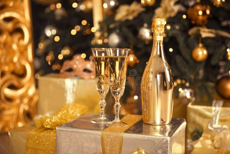Botella de oro de Champán con dos vidrios Concepto de la celebración de la Navidad imagenes de archivo