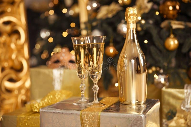 Botella de oro de Champán con dos vidrios Concepto de la celebración de la Navidad fotos de archivo