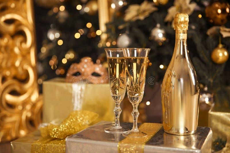 Botella de oro de Champán con dos vidrios Concepto de la celebración de la Navidad foto de archivo libre de regalías