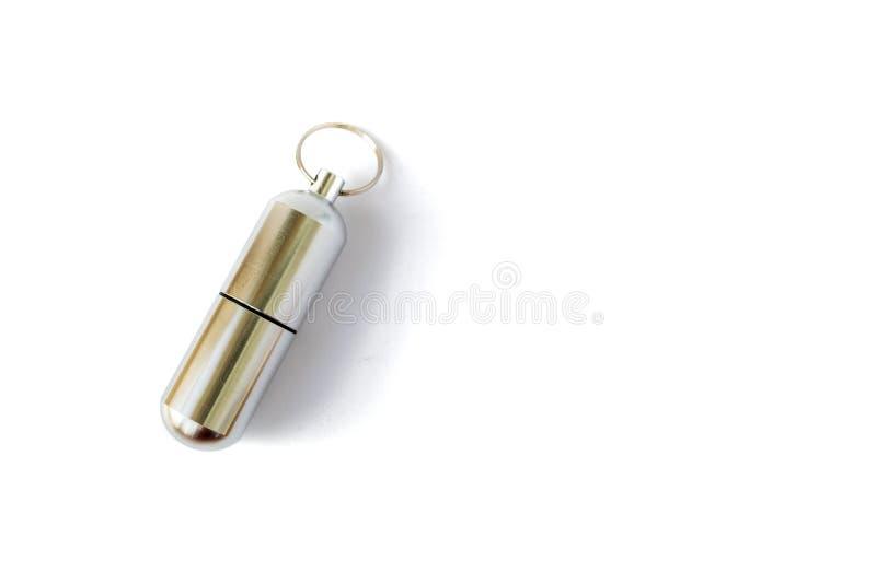 Botella de píldora de aluminio cerrada con un llavero, aislado en el fondo blanco Botella del llavero para almacenar la medicina foto de archivo libre de regalías