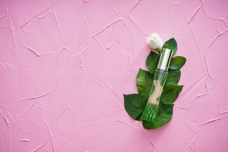 Botella de perfume con la rosa y las hojas hermosas en fondo texturizado color fotografía de archivo libre de regalías