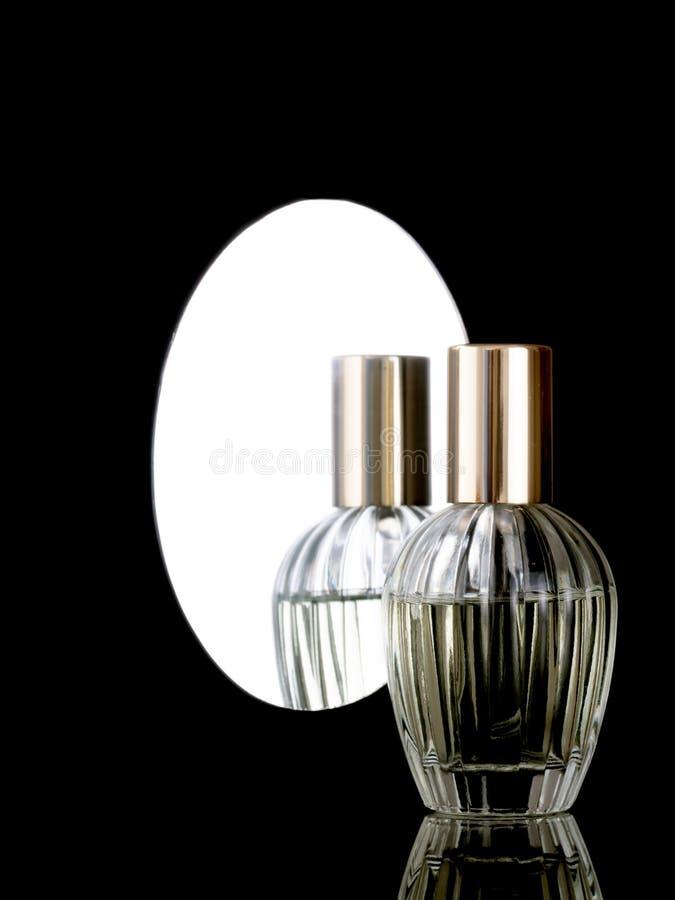 Botella de perfume de cristal clara elegante en un fondo negro brillante con la reflexión también en espejo detrás con el copyspa imagen de archivo libre de regalías