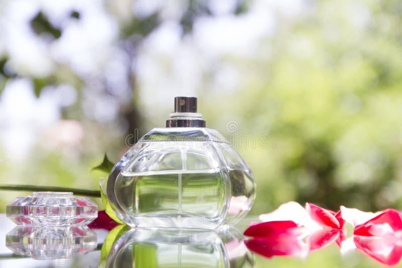Botella de perfume en naturaleza con Rose Petals imagen de archivo