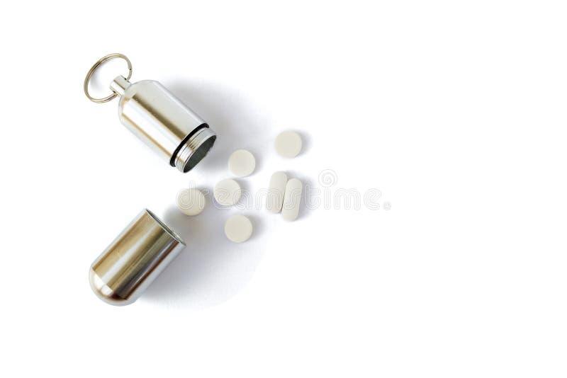 Botella de plata de la medicina con las píldoras blancas al lado de ella, aislado en el fondo blanco Contenedor portátil del llav foto de archivo libre de regalías
