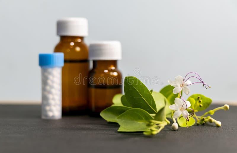 Botella de remedios homeopáticos que consisten en las píldoras hechas de una sustancia inerte - sugarlactose y homeopático líquid foto de archivo libre de regalías
