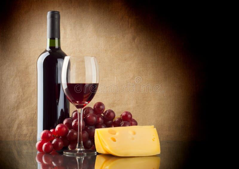 Botella de rojo, un manojo de uvas rojas y un pedazo de queso imagenes de archivo