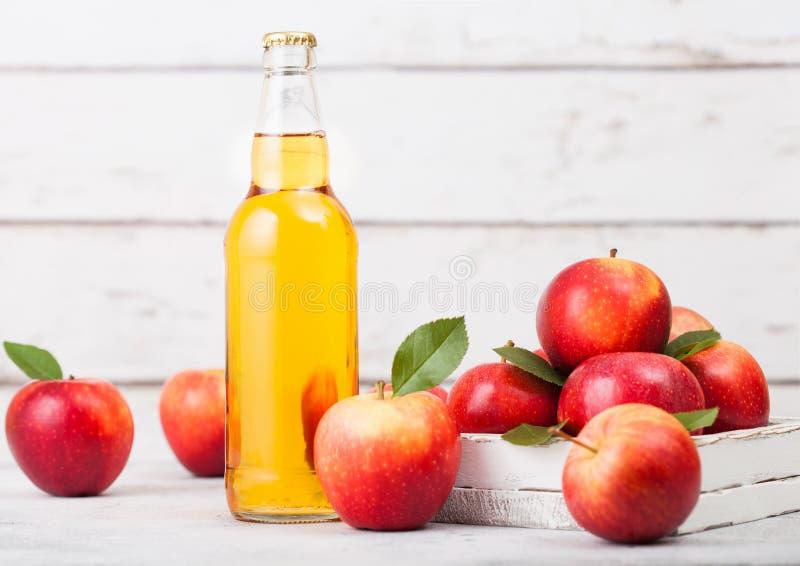 Botella de sidra de manzana orgánica hecha en casa con las manzanas frescas en caja en fondo de madera Espacio para el texto imagenes de archivo