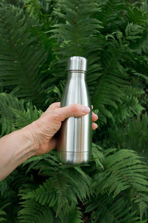 Botella de termo inoxidable reutilizable para el agua en la mano femenina para llenar las reservas del agua del cuerpo contra la  foto de archivo libre de regalías