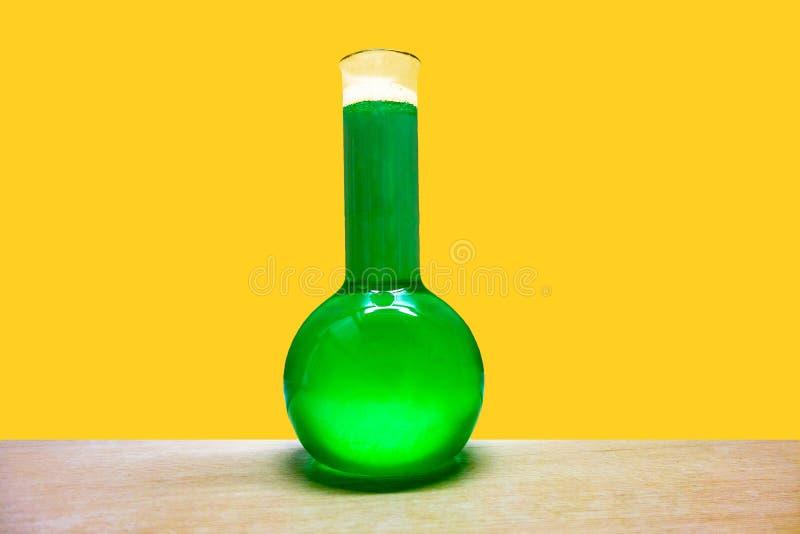 Botella de vidrio química de la réplica con el líquido verde envenenado en fondo amarillo de la pared foto de archivo libre de regalías