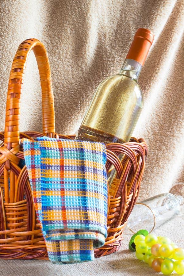 Botella de vino blanco, de servilleta y de manojo de uvas en una cesta de mimbre foto de archivo