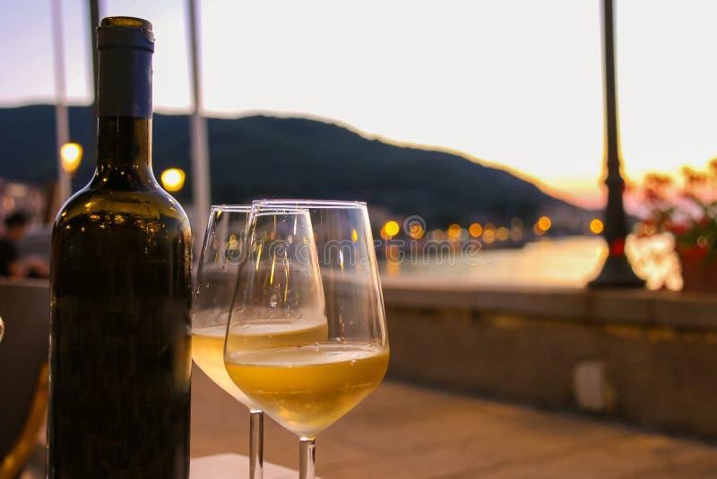Botella de vino blanco y de dos vidrios en la tabla del restaurante fotos de archivo libres de regalías