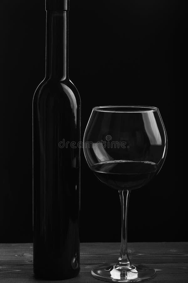 Botella de vino cerca del vidrio en fondo negro imagen de archivo libre de regalías