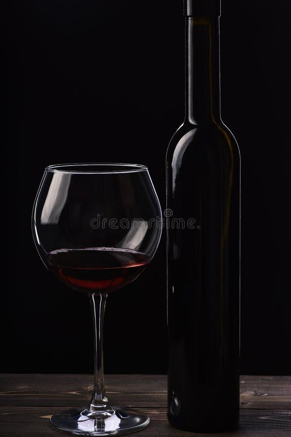 Botella de vino cerca del vidrio en fondo negro fotos de archivo libres de regalías