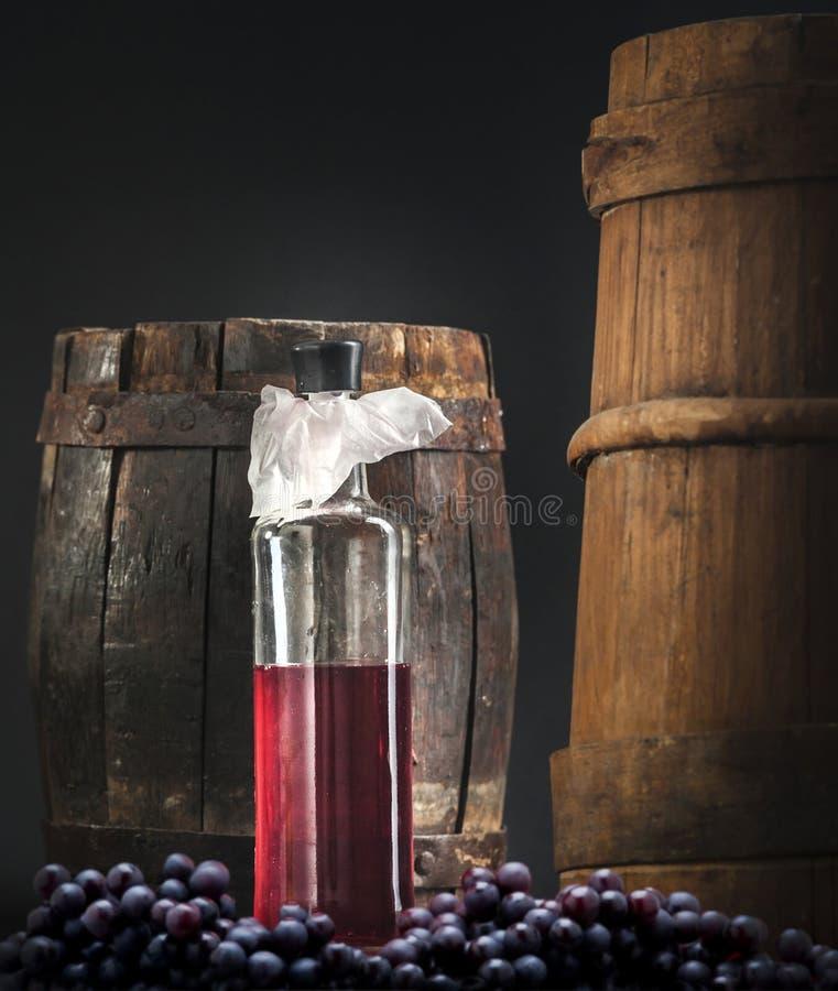 Botella de vino con las uvas y el barril fotos de archivo