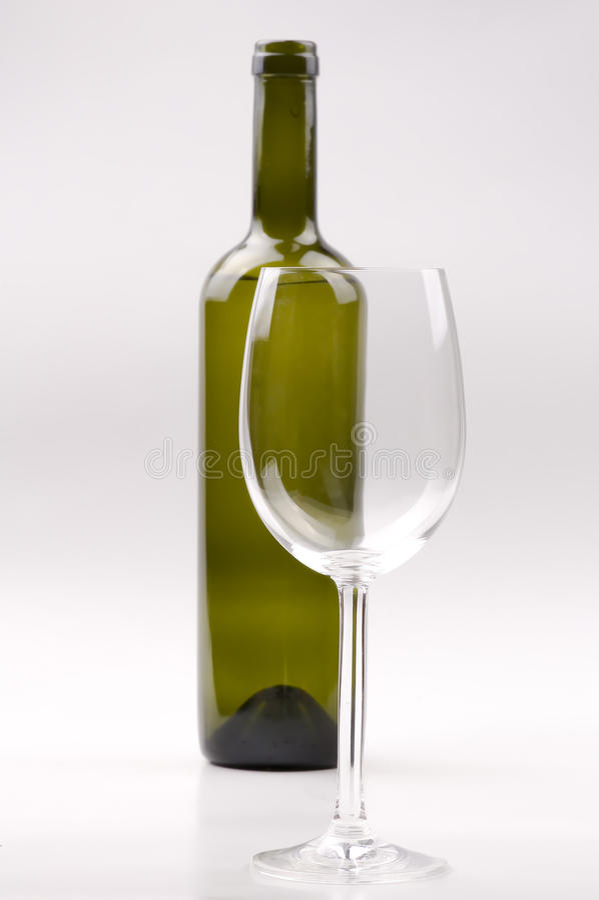 Botella de vino, copa cristalina aislada en blanco foto de archivo