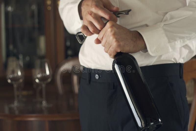 Botella de vino de la abertura del Sommelier fotografía de archivo libre de regalías