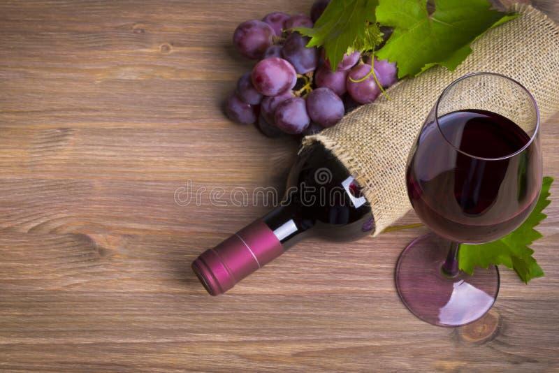 Botella de vino, de uva roja y de vidrio en la tabla de madera fotos de archivo