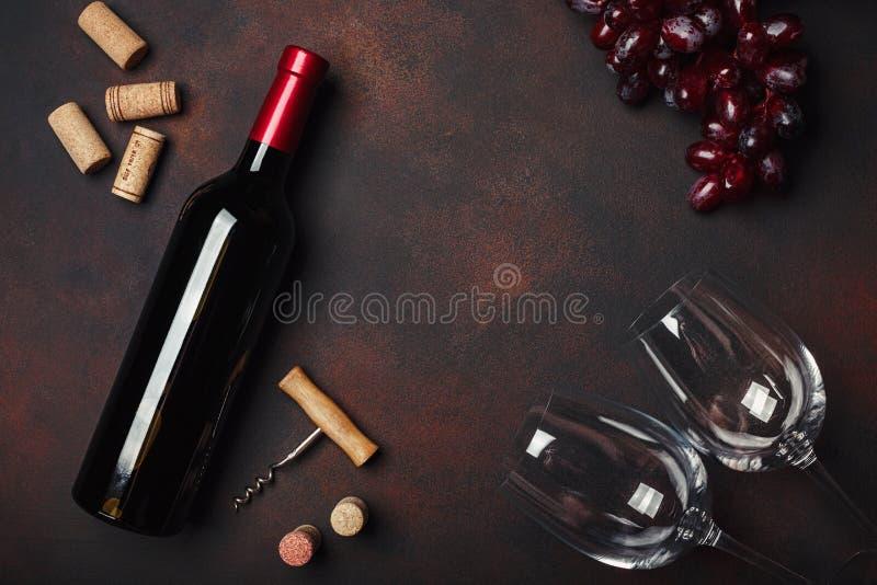 Botella de vino, dos vidrios, sacacorchos y corchos, en backg oxidado imagenes de archivo