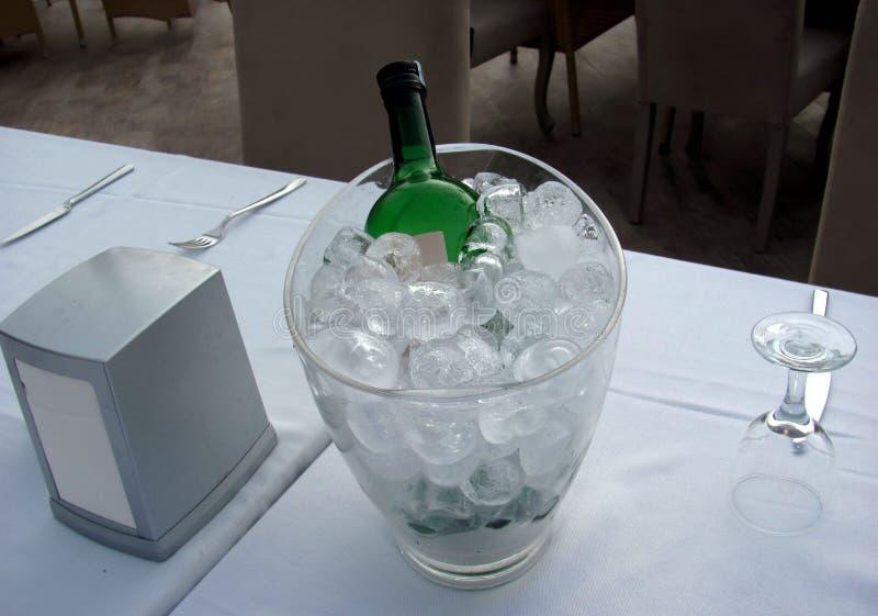 Botella de vino en una jarra de cristal en una tabla en un restaurante imagenes de archivo