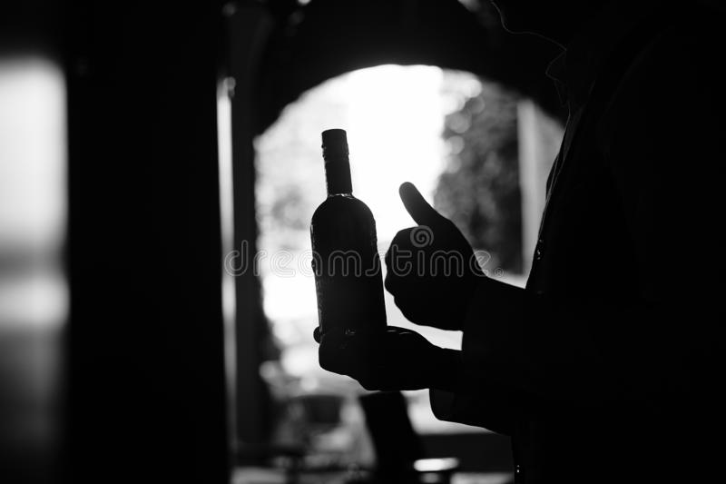 Botella de vino en una mano en el túnel oscuro imagen de archivo