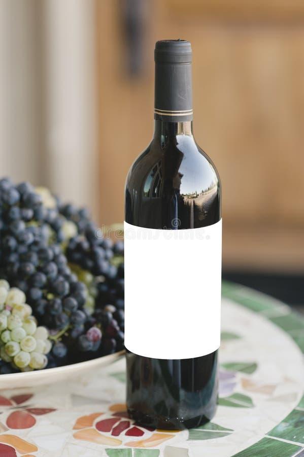 Botella de vino en una tabla con la etiqueta en blanco imagen de archivo libre de regalías