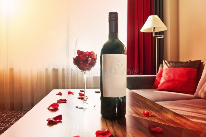 Botella de vino en una tabla en la puesta del sol en casa foto de archivo libre de regalías