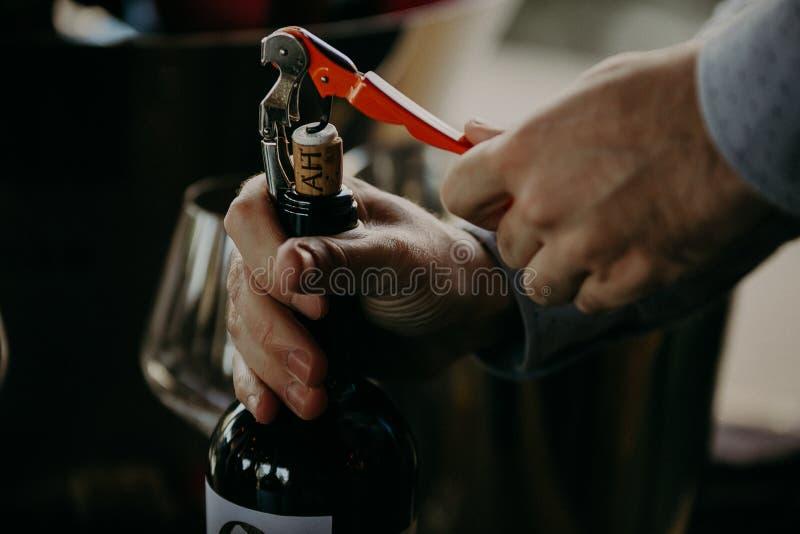 Botella de vino de la abertura del Sommelier en la bodega fotografía de archivo libre de regalías