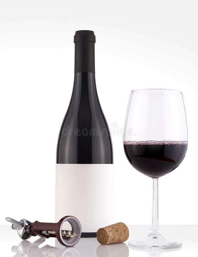 Botella de vino rojo aislada en un fondo blanco, una etiqueta blanca de la etiqueta y un vidrio imágenes de archivo libres de regalías