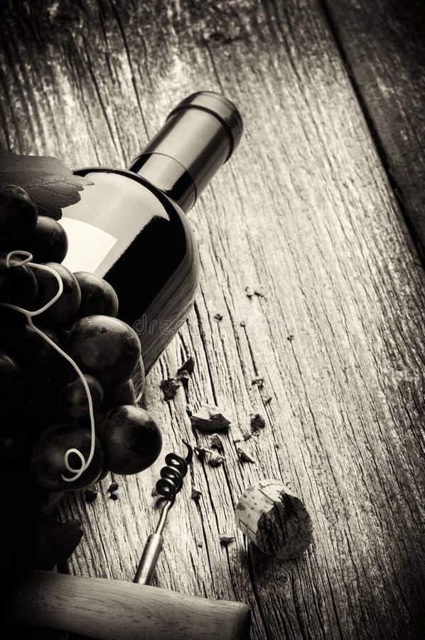 Botella de vino rojo con la uva y el sacacorchos frescos foto de archivo