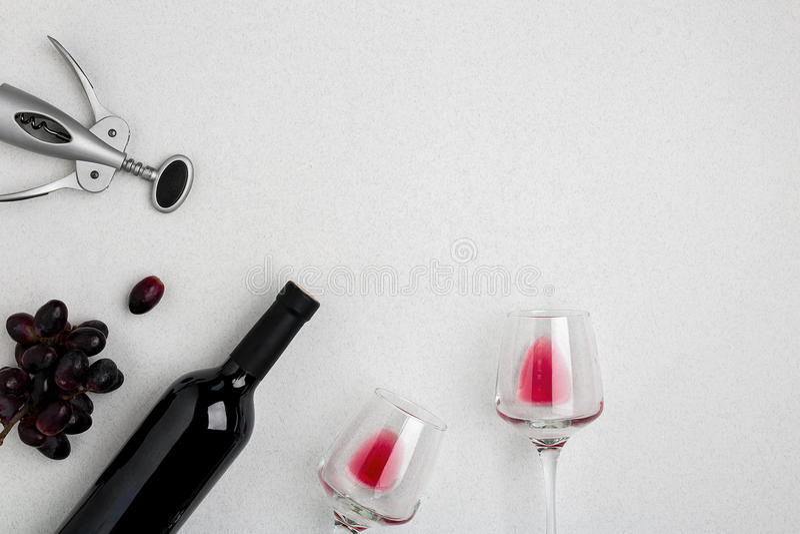 Botella de vino rojo con los vidrios en la maqueta blanca de la opinión superior del fondo fotos de archivo