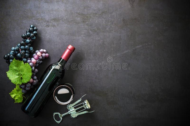 Botella de vino rojo, de copa y de uvas foto de archivo