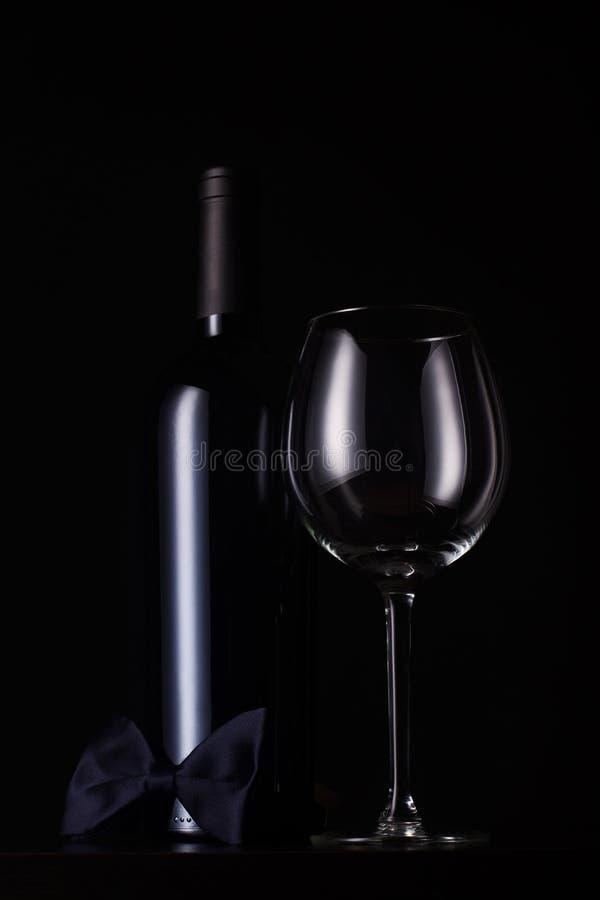 Botella de vino rojo negra con el vidrio alto vacío fotos de archivo libres de regalías
