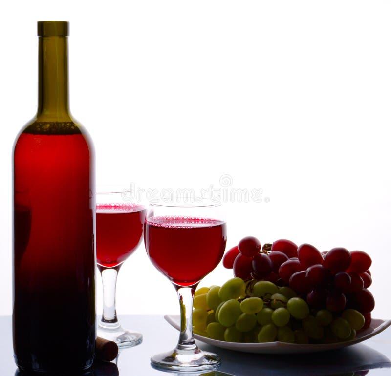 Botella de vino rojo y de uvas dulces imagenes de archivo