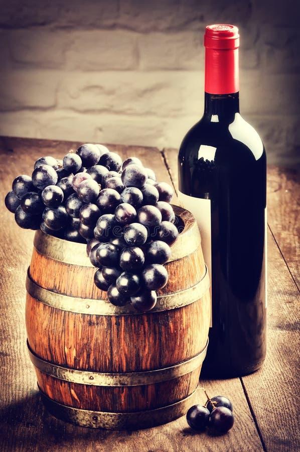 Botella de vino rojo y manojo de uva imágenes de archivo libres de regalías