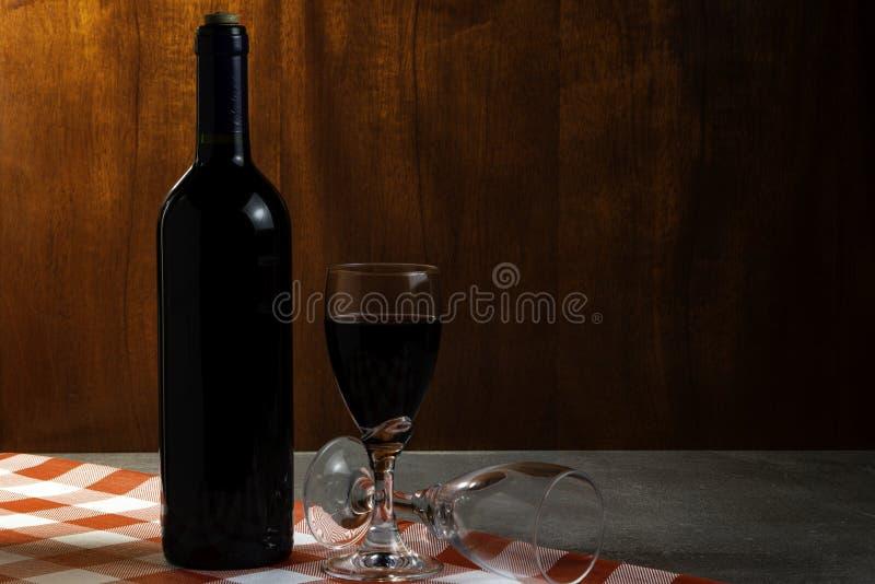 Botella de vino tinto en la bodega para probar Fondo de madera rojo Tradición del vino y concepto de la cultura imagen de archivo libre de regalías
