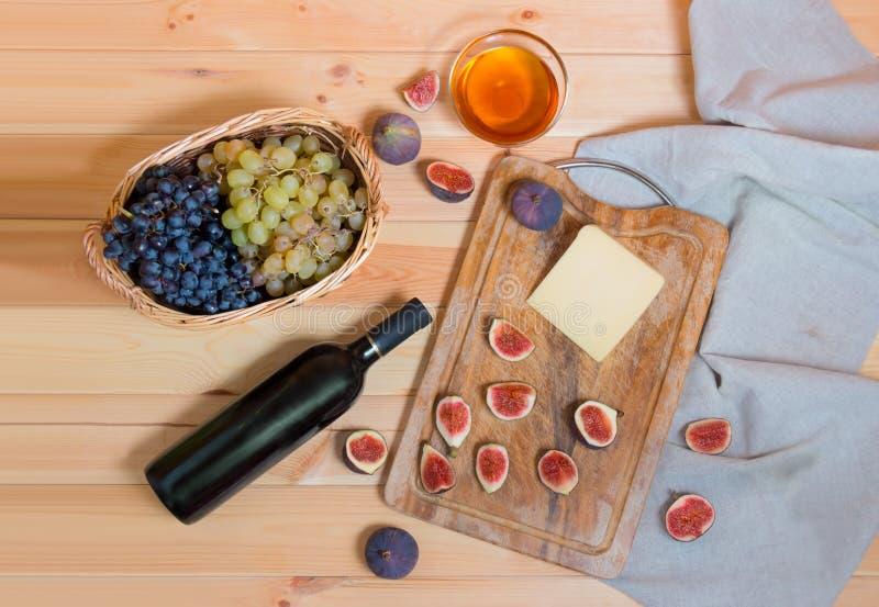 Botella de vino tinto, higos, queso, manojos de uva y miel en la tabla de madera fotos de archivo