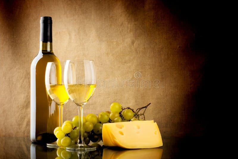 Botella de vino, un manojo de uvas blancas y un pedazo de queso fotos de archivo