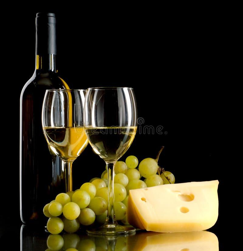 Botella de vino, un manojo de uvas blancas y un pedazo de queso fotos de archivo libres de regalías