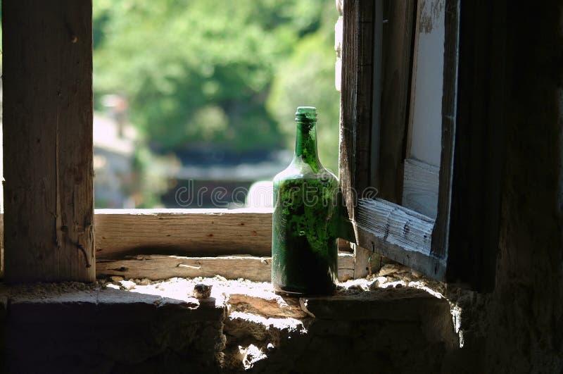 Botella de vino verde vieja en ventana fotografía de archivo