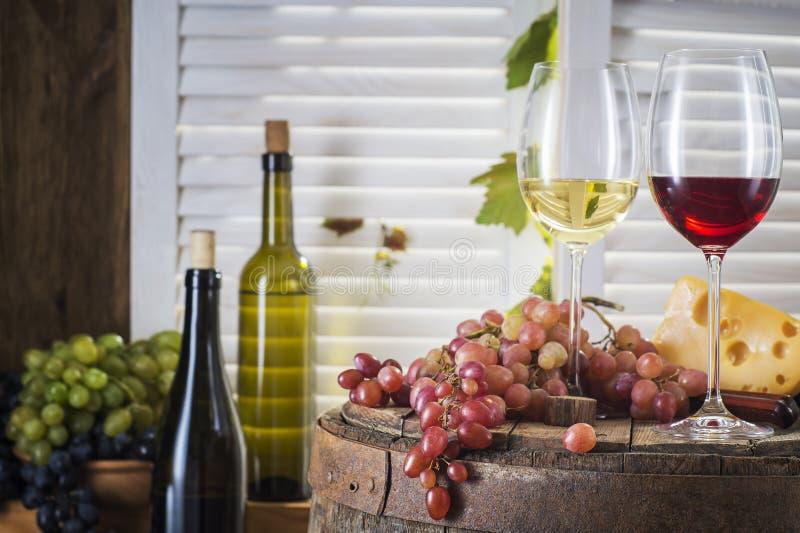 Botella de vino, vidrio de vino blanco con queso y uva imágenes de archivo libres de regalías
