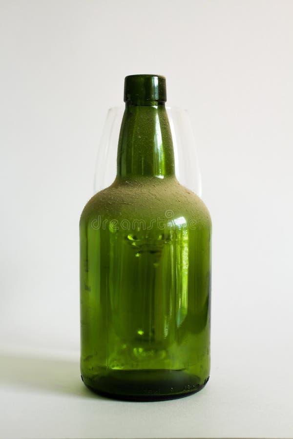 Botella de vino vieja del verde del polvo en blanco fotografía de archivo