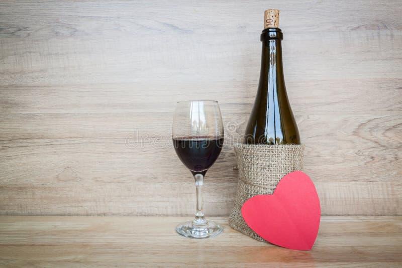 Botella de vino y de copa de vino con el corazón en el fondo de madera foto de archivo