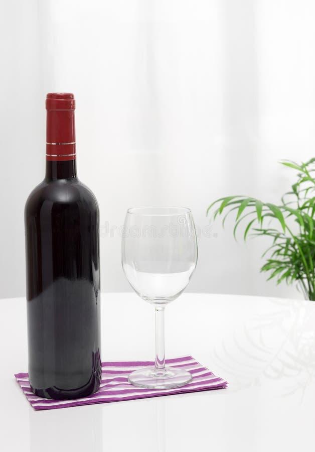 Botella de vino y de vidrio en la tabla foto de archivo libre de regalías