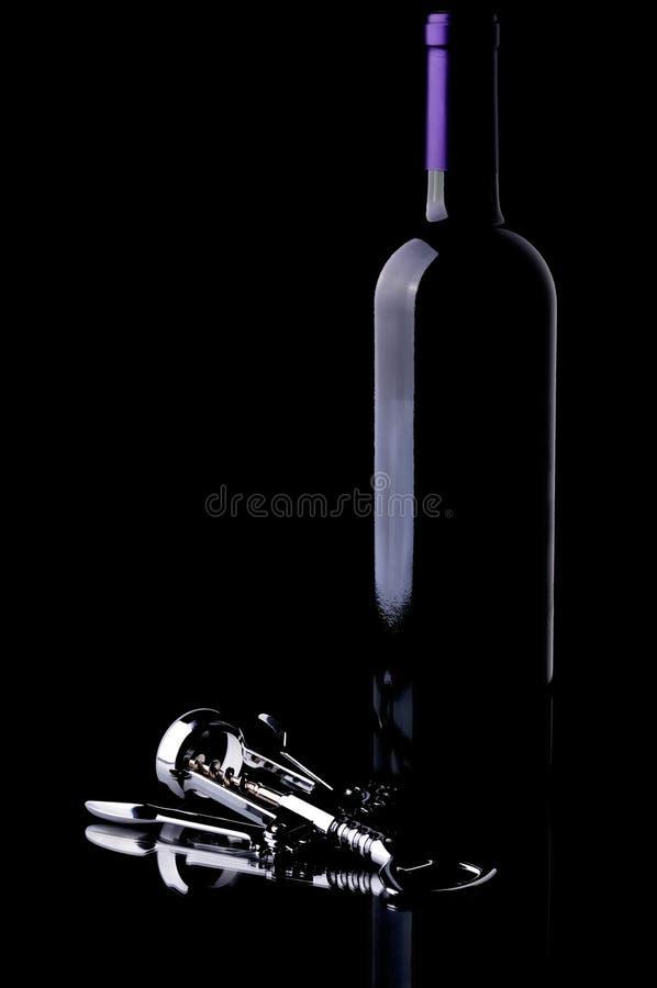 Botella de vino y sacacorchos del cromo en negro imagen de archivo libre de regalías