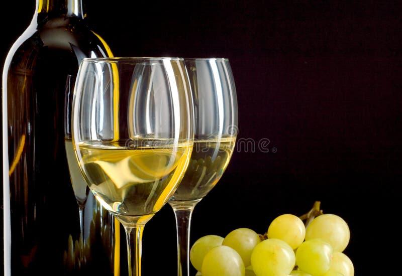 Botella de vino y un manojo de uvas blancas fotografía de archivo libre de regalías