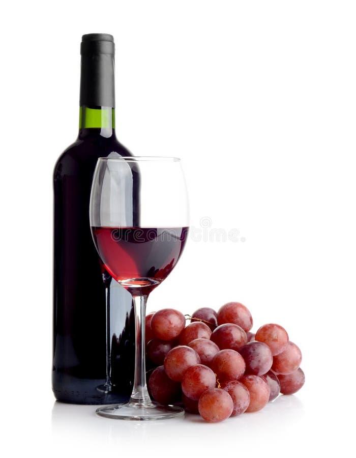Botella de vino y un manojo de uvas rojas fotografía de archivo