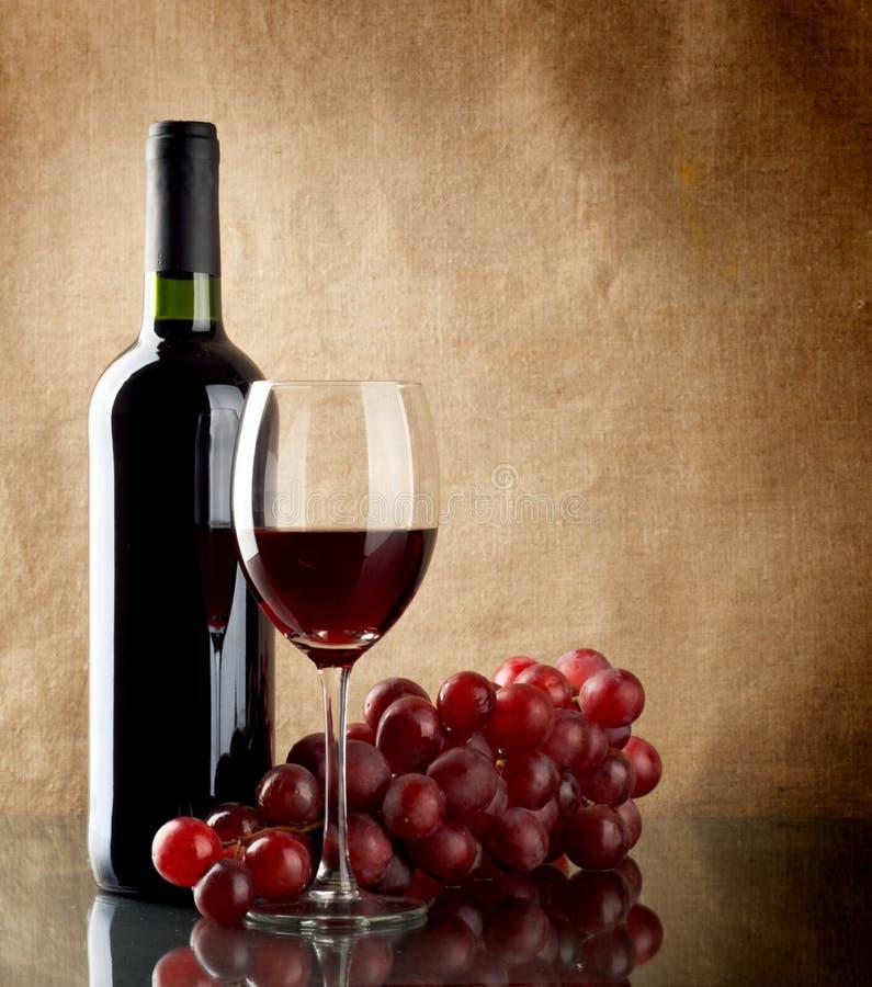 Botella de vino y un manojo de uvas rojas imagen de archivo