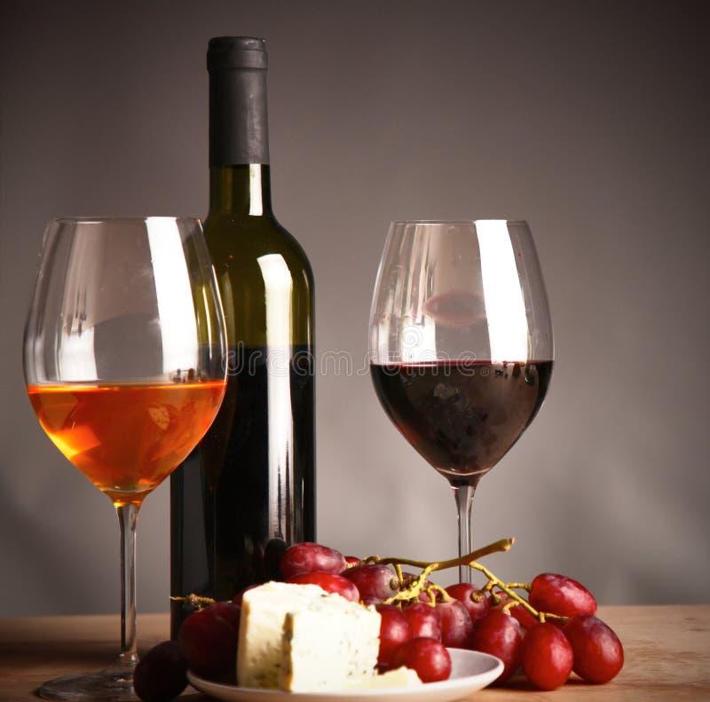 Botella de vino y de vidrio en la tabla foto de archivo