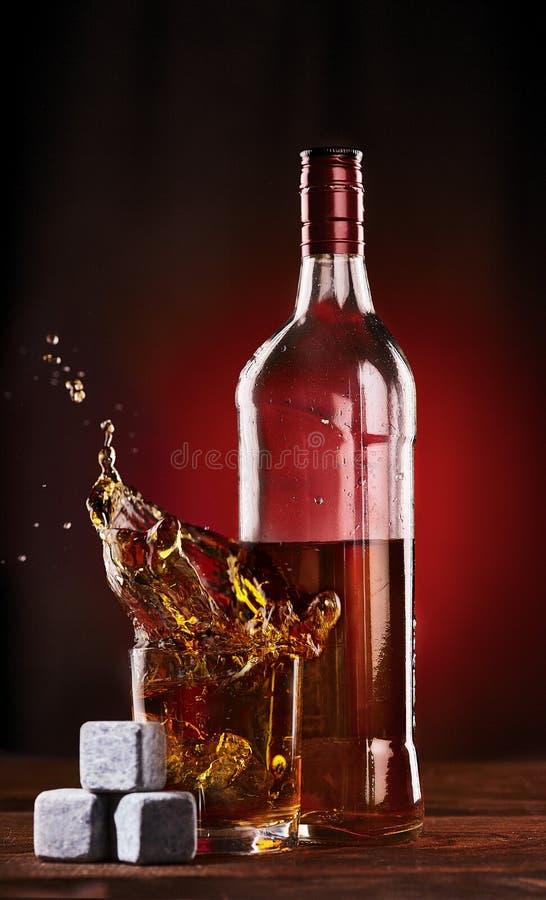 Botella de whisky con salpicar de cristal sobre las piedras de hielo para el whisky fotos de archivo libres de regalías