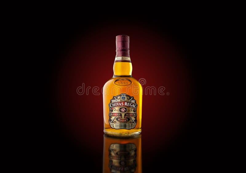 Botella de whisky del ` de Chivas Regal del ` con el contraluz rojo oscuro imagen de archivo